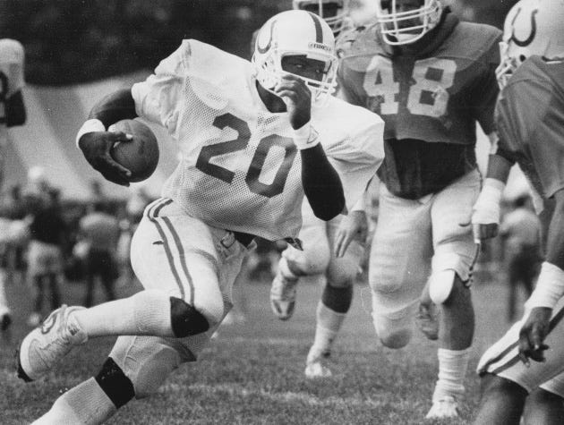 Running back Albert Bentley (20) cuts to a hole and heads upfield during a 1986 practice session at training camp as Jeff Leading (48) defends.
