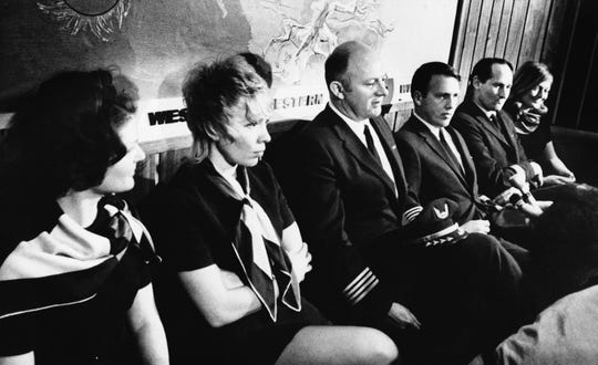 The crew of a Western Airlines jetliner talk about how a 19-year-old U.S. Army inductee from California hijacked a flight from San Francisco to Seattle, Feb. 26, 1971, Seattle, Wash. The crew is from left to right are Linda LaPorte, Capt. Bruce DeSpain, First Officer Gary Gottschalk, Second Officer Allen Pilgeram, and Susan Methonen. (AP Photo)