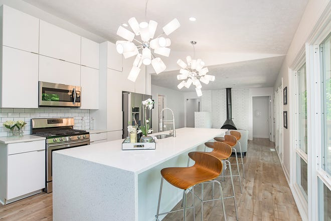 The kitchen features sleek new, 9-foot-tall cabinets as well as additional seating for at least four.