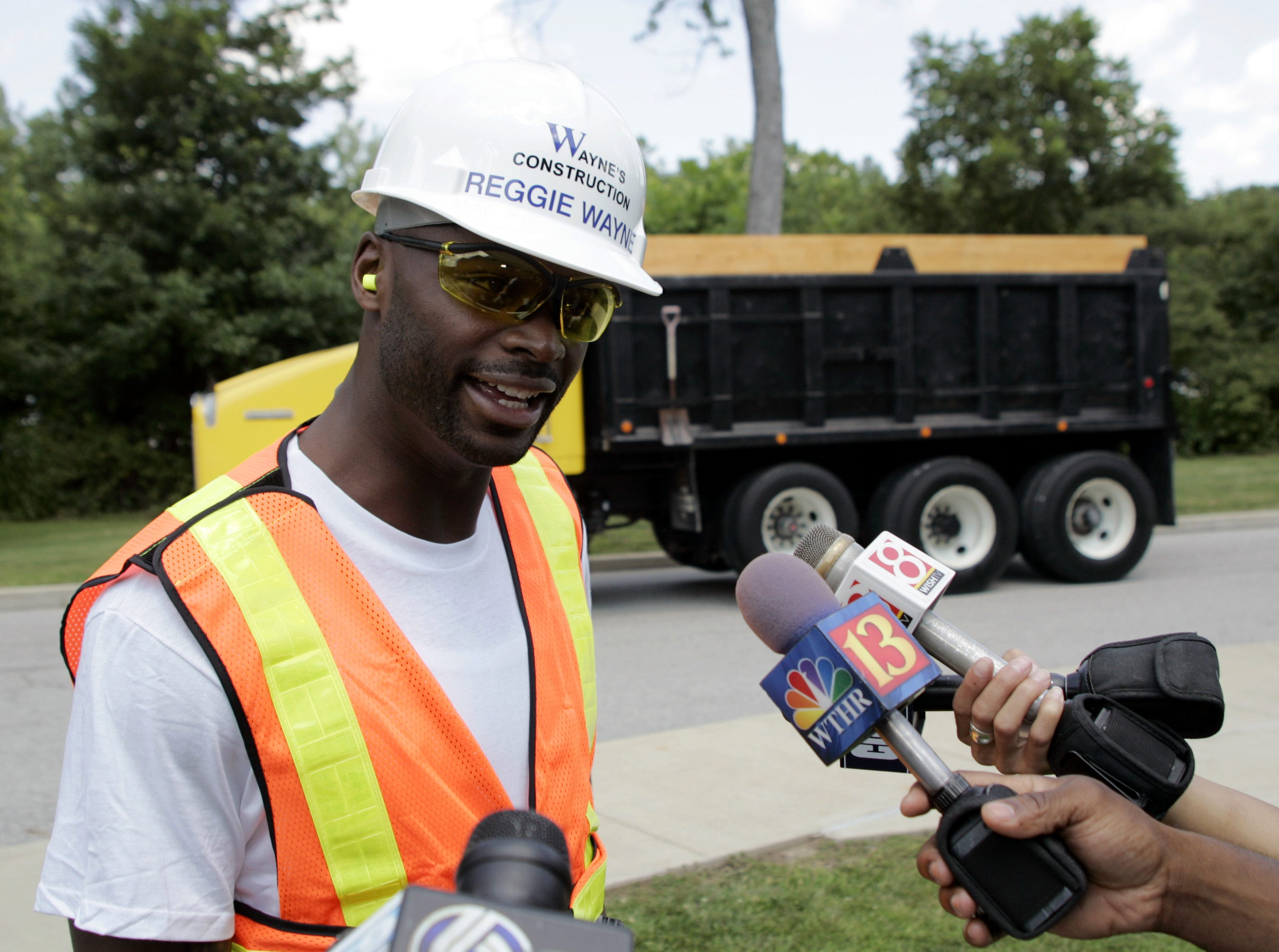 Indianapolis Colts wide receiver Reggie Wayne talks to the media after arriving at the Colts NFL football training camp in a rented dump truck in Terre Haute, Ind., Sunday, Aug. 2, 2009.