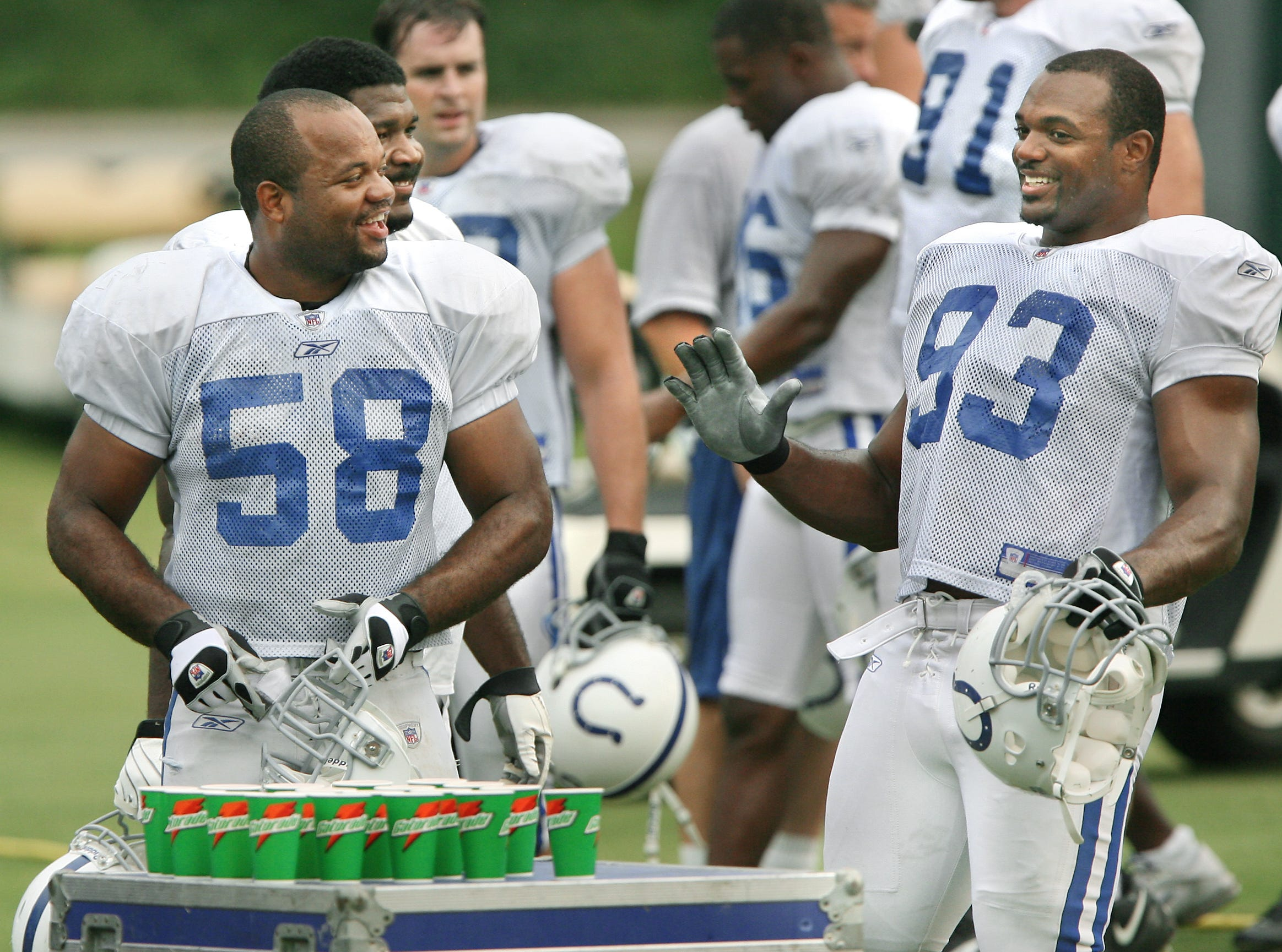 (From left) Colts linebacker Gary Brackett shares a laugh with teammate and defensive end Dwight Freeney as they take a water break during practice at Rose Hulman Institute of Technology on Wednesday, August 15, 2007.
