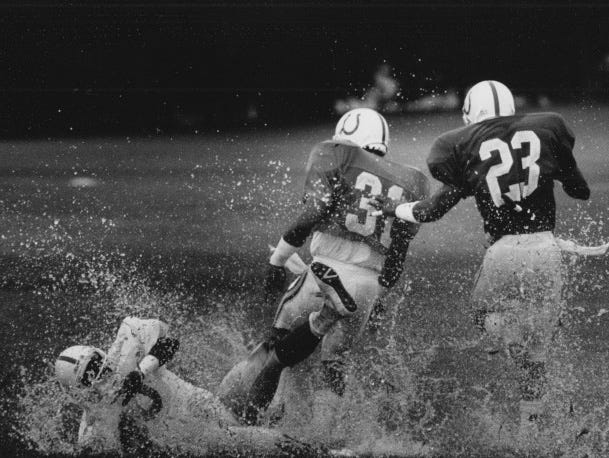 A shower soaked Colts training camp at Anderson university in 1989. Joey Clinkscales gets out in the spray as he dives for a pass. Defending are Michael Ball (31) and Bruce Plummer (23)