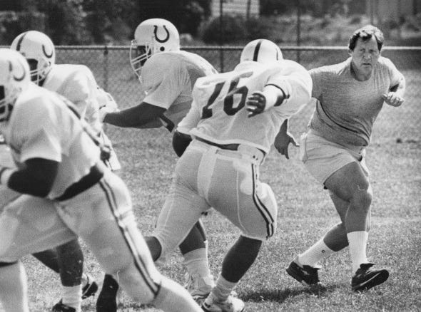 Coach Rod Dowhower assumes the role of defensive rusher to show the offensive linemen where they should be going on a particular play during Colts training camp in 1986.