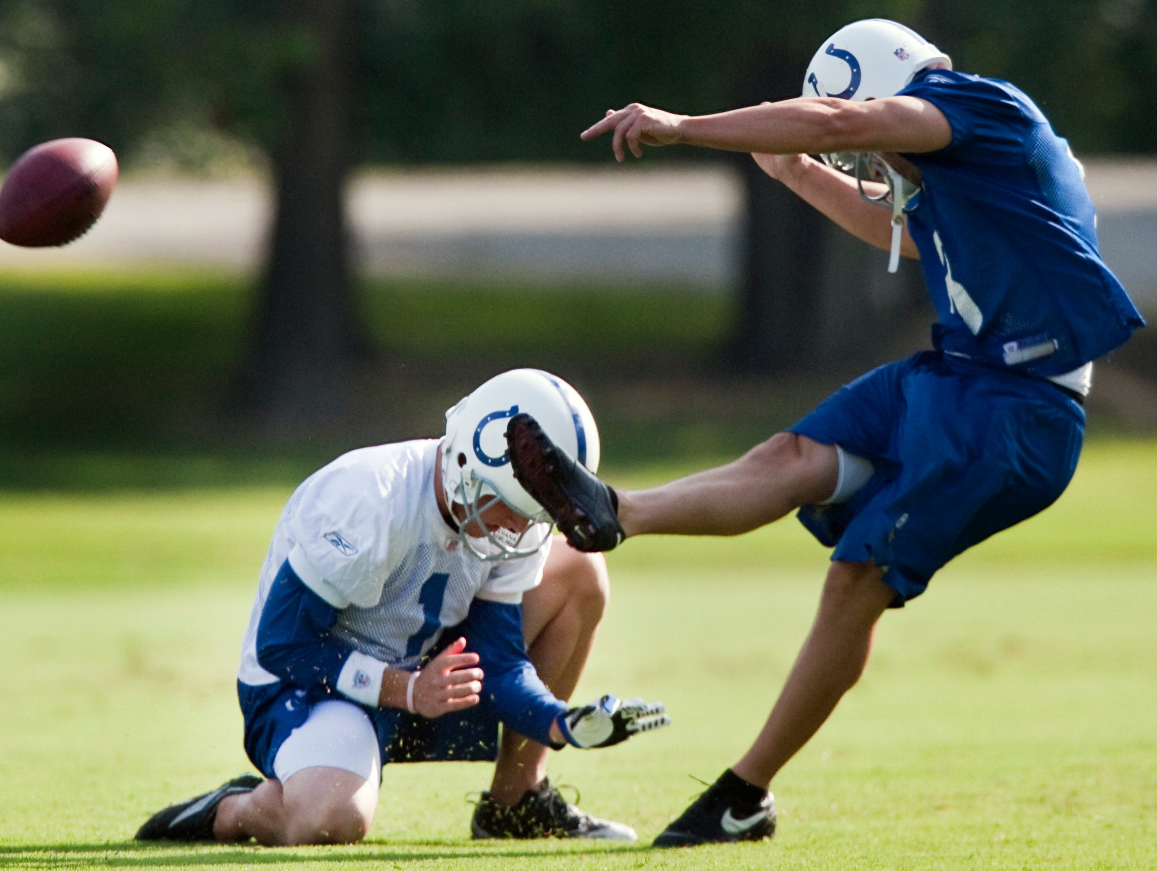 Indianapolis Colts rookie punter Pat McAfee (1), left, holds for a field goal attempt during practice for fellow rookie kicker Shane Andrus (8), right, during the team's first morning of practice during training camp at Rose-Hulman Institute of Technology, Terre Haute, Ind., Monday, August 3, 2009.