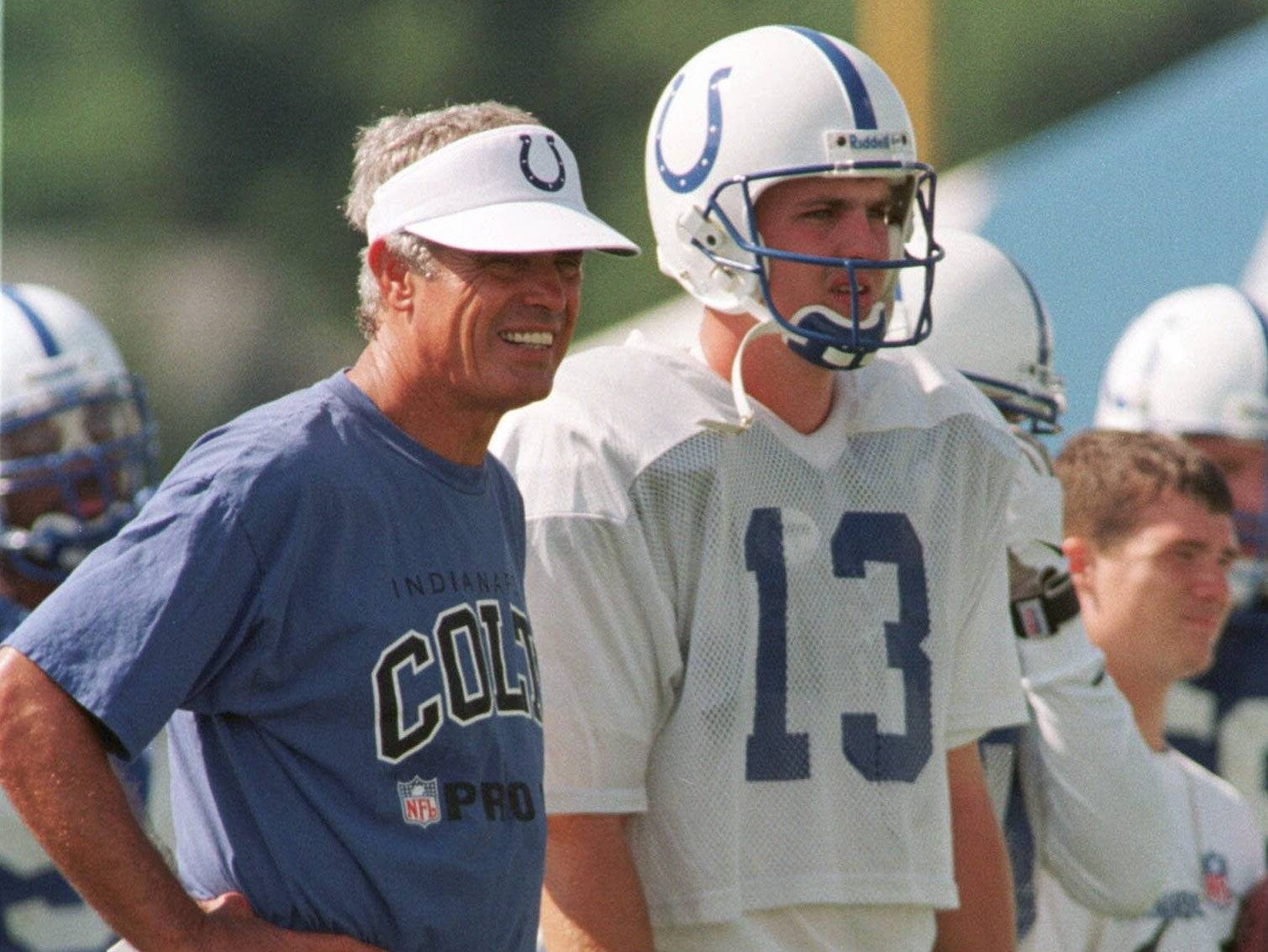 Indianapolis Colts' head coach Jim Mora, left, watches practice with quarterback Kelly Holcomb during the team first practice in training camp at Anderson University in Anderson, Ind., Friday,, July 24, 1998.  The Colts' first round pick, quarterback Peyton Manning, has yet to sign a contract with the team.