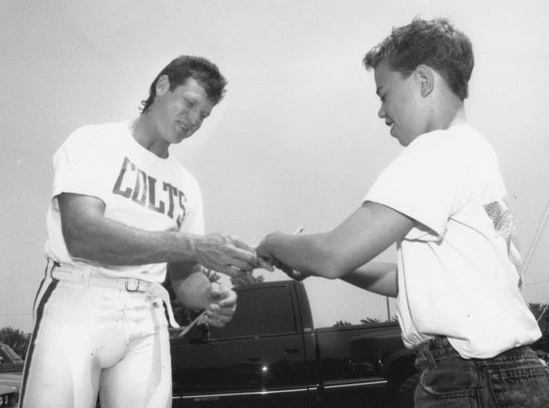 Rusty Hilger obliges 11-year-old Evan Rumley with an autograph before heading to the practice field during Colts camp at Anderson University in 1991.