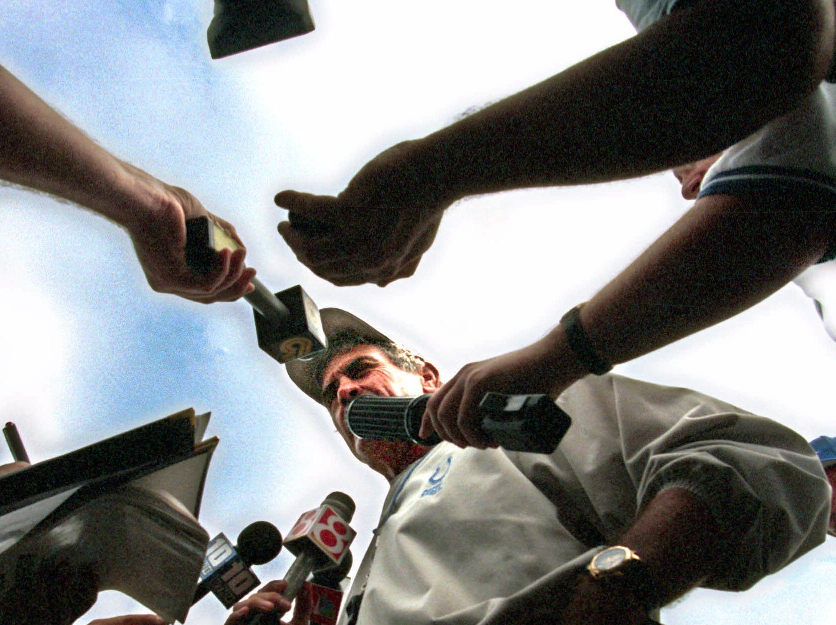 Indianapolis Colts coach Jim  Mora is surrounded by microphones and television cameras after the last day of training camp at the Rose - Hulman Institute of Technology, in Terre Haute, Ind., Thursday, Aug. 19, 1999. Mora said that he was generally satisfied with the progress of the team during the camp.