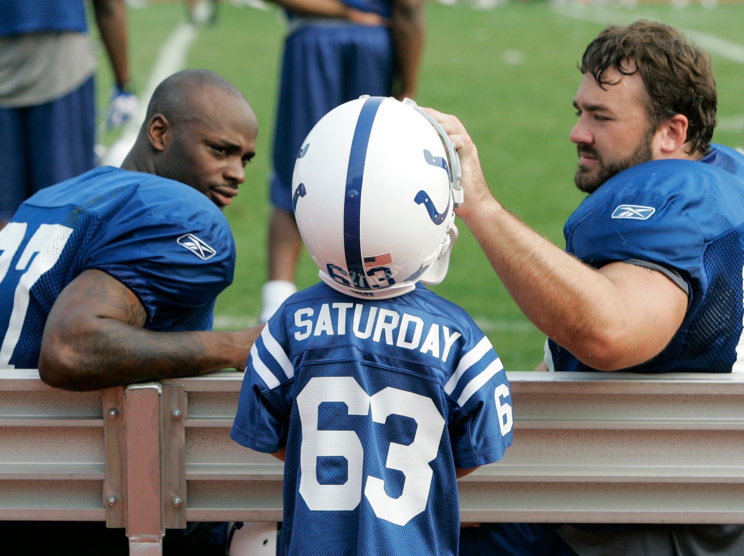 Indianapolis Colts wide receiver Reggie Wayne, left, watches as center Jeff Saturday puts his helmet on his son Jeff Saturday Jr., 6, during a scrimmage at the team's football training camp in Terre Haute, Ind., Saturday, Aug. 4, 2007.