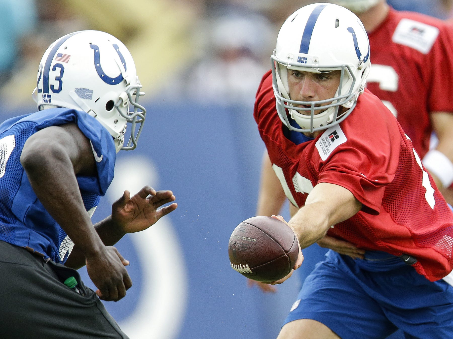 Indianapolis Colts quarterback Andrew Luck (12) hands off to running back Frank Gore (23) during the Indianapolis Colts NFL training camp at Anderson University on July 28, 2016.