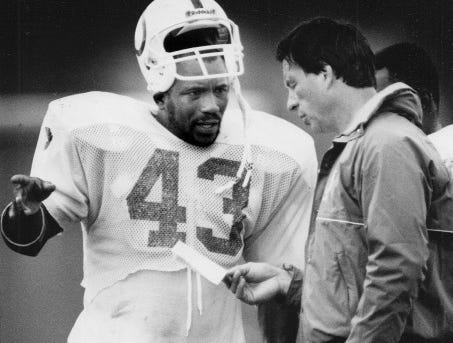 Ernest Jackson has a word with running back coach Leon Burtnett during Colts workout in 1989.