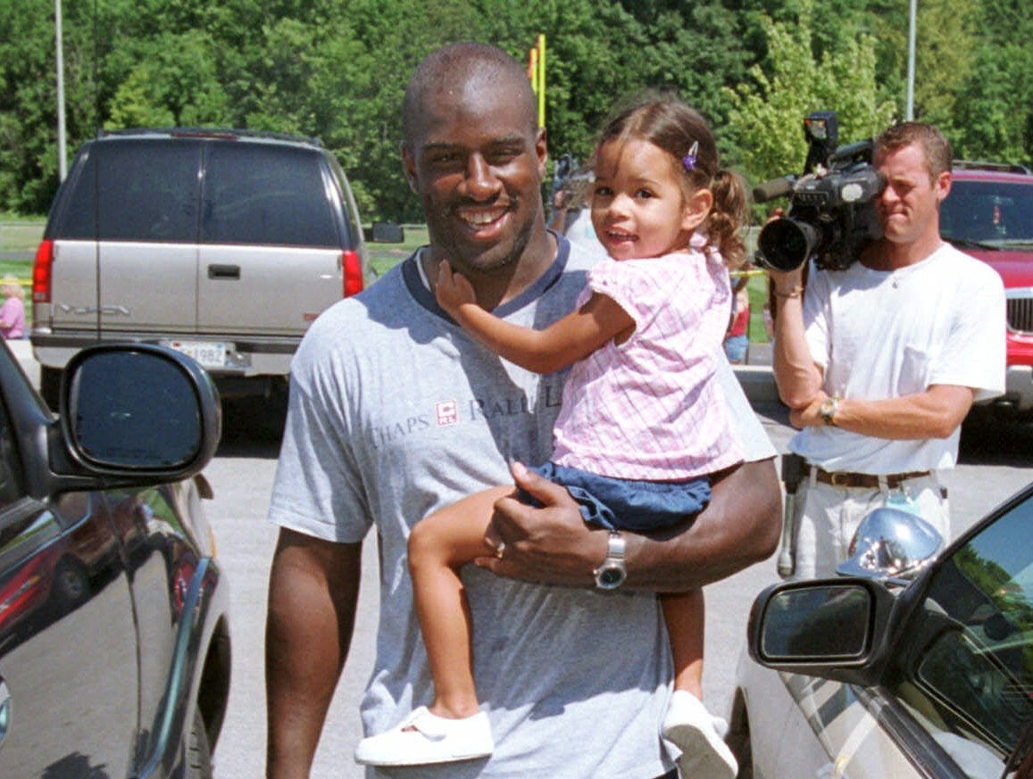 Indianapolis Colts running back Paul Shields carries his daughter Jordan to his car following the end of training camp in Terre Haute, Ind. Thursday Aug. 10, 2000.