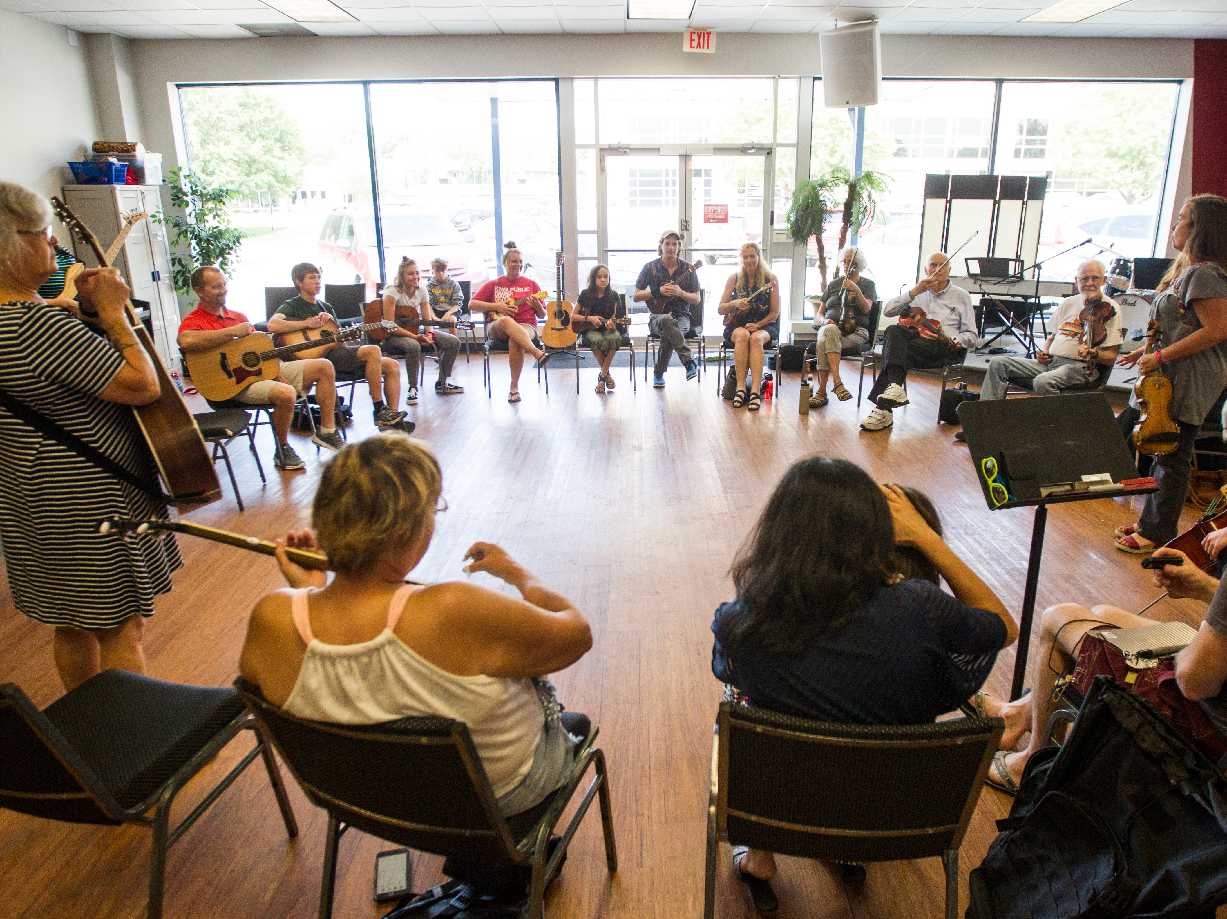 """Savage Hearts trio members, Tracy Lynn, far left, and Annie Savage, far right, give instructions during a free """"Learn to Jam Bluegrass Workshop"""" on Wednesday, July 25, 2018, at West Music in Coralville, Iowa. Savage was joined by the other two members of the Savage Hearts trio during the two hour workshop."""