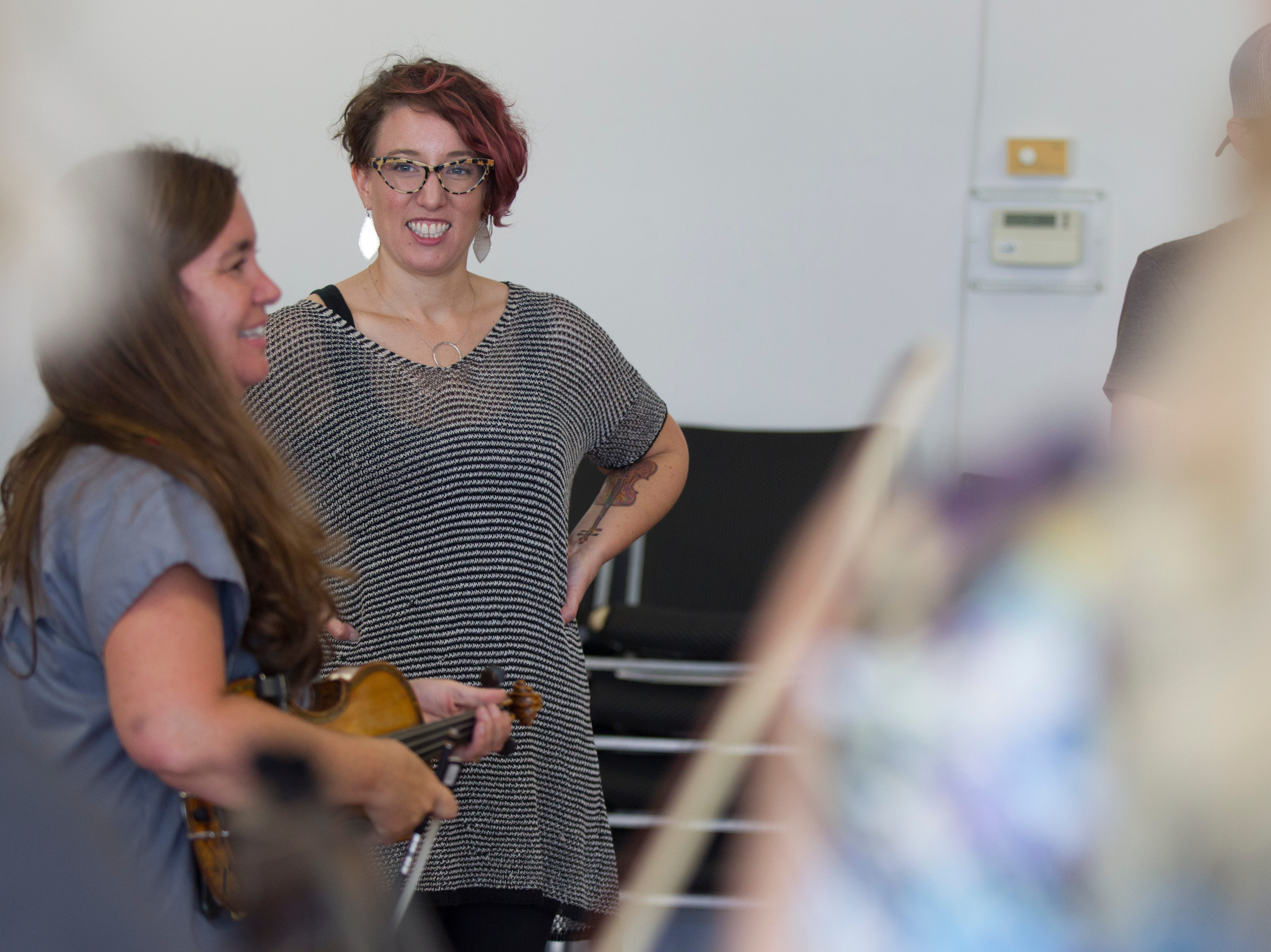 """Katie Senn, West Music content and community engagement manager and Awful Purdies cellist, listens to Annie Savage give instructions during a free """"Learn to Jam Bluegrass Workshop"""" on Wednesday, July 25, 2018, at West Music in Coralville, Iowa. Savage was joined by the other two members of the Savage Hearts trio during the two hour workshop."""