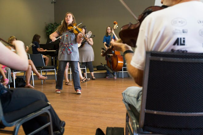 """Annie Savage, Liberty High orchestra teacher, plays during a free """"Learn to Jam Bluegrass Workshop"""" on Wednesday, July 25, 2018, at West Music in Coralville, Iowa. Savage was joined by the other two members of the Savage Hearts trio during the two hour workshop."""