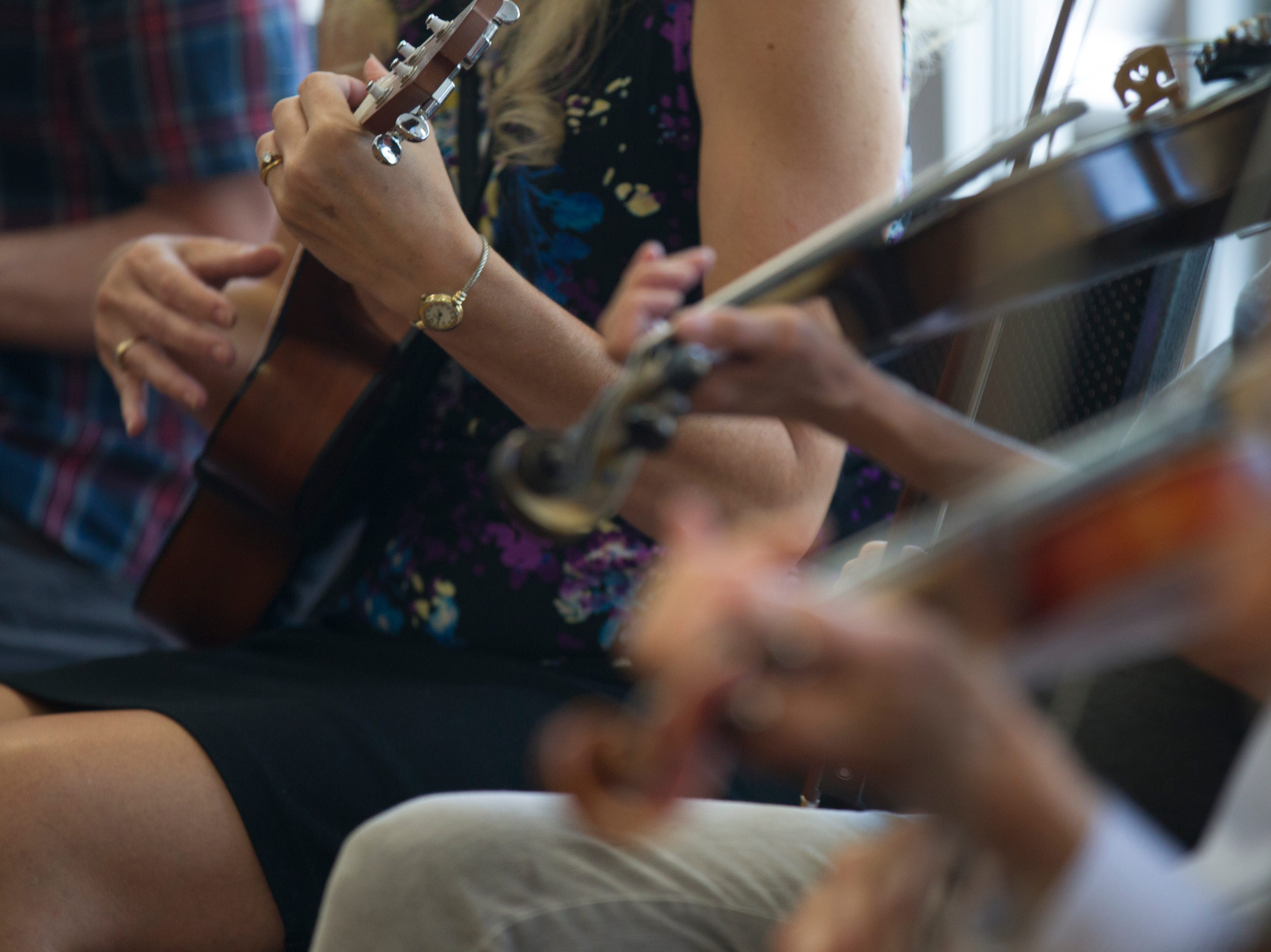 """Workshop participants play along during a free """"Learn to Jam Bluegrass Workshop"""" on Wednesday, July 25, 2018, at West Music in Coralville, Iowa. Savage was joined by the other two members of the Savage Hearts trio during the two hour workshop."""