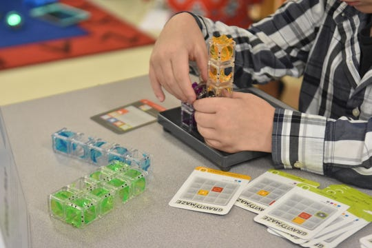 A student works on a task in a classroom.