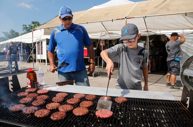 Colten Guynn, 11, flips burgers under the watchful eye of Mark Walters at the Tippecanoe Cattlemens Association tent Wednesday, July 25, 2018, at the Tippecanoe County 4-H Fair in Lafayette. Guynn, who will be a sixth grade student at Southwestern Middle School in the fall, is showing beef at the fair.