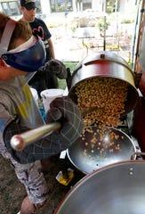 Eagle-Gazette reporter Jeff Barron dumps a batch of kettle corn Wednesday, July 25, 2018, in downtown Lancaster.