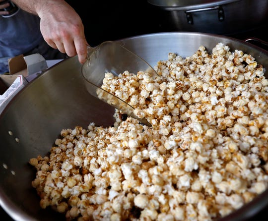 Eric Pistole gives a final mix to kettle corn made by Eagle-Gazette reporter Jeff Barron Wednesday, July 25, 2018, in downtown Lancaster.