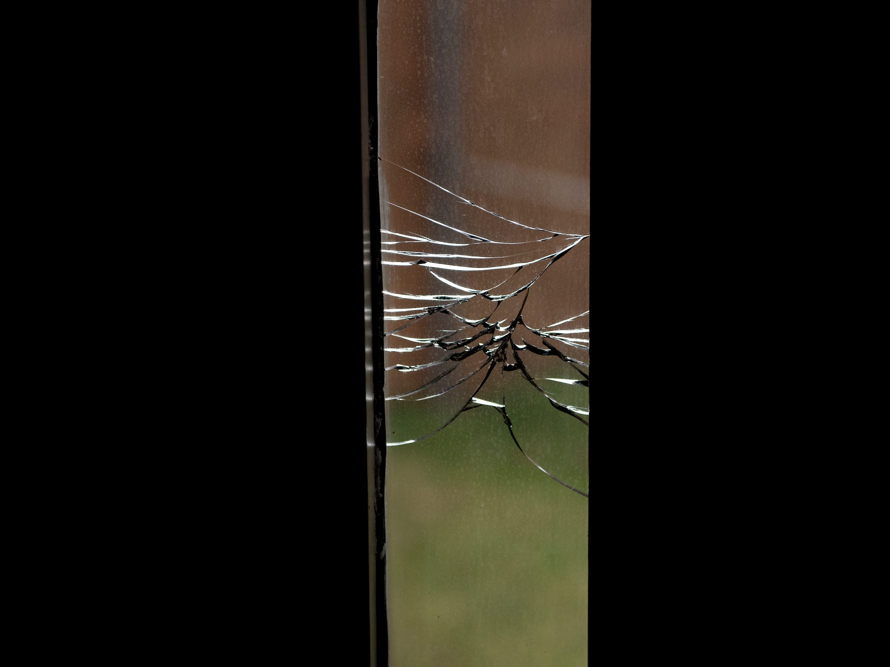 A cracked window in an area of the facility not in use  photographed  during a tour of the Ingham County Jail on Tuesday, April 24, 2018, in Mason.