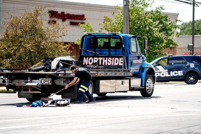 A Northside Towing employee cleans up debris from a crash in the intersection of Cedar Street and Jolly Road on Wednesday, July 25, 2018, in Lansing.