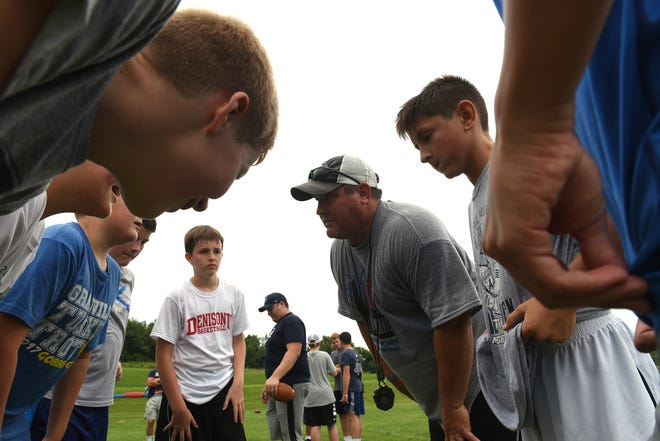 Granville High School's head football coach Justin Buttermore talks to a group of middle school students during the program's youth football camp on Tuesday, July 24, 2018.