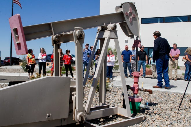 Community members gather to thank New Mexico State Land Office Commissioner Aubrey Dunn for donating a replica pumpjack to the San  Juan College School of Energy Wednesday during a ceremony in front of the school in Farmington.
