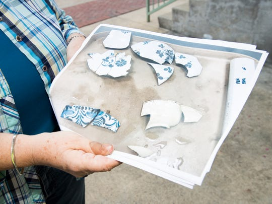 Elizabeth Benchley, director of the University of West Florida Archaeology Institute, shows a photograph of pottery recently discovered in the remains of a well along Jefferson Street as Gulf Power continues its utility work in downtown Pensacola.