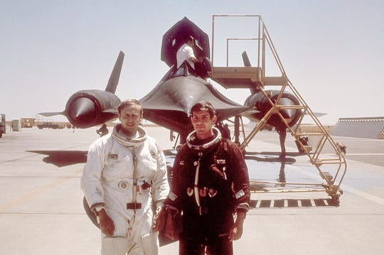 U.S. Air Force pilot Joe Kinego, right, stands in front of an SR-71 aircraft.