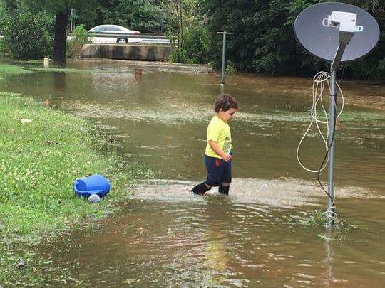 Keandre Gonzalez's sliding board is in Burd Run on Wednesday, July 25, 2018. Flood waters barely go under Walnut Bottom Road (Pa. 174) in the background.