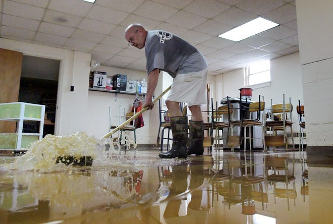 Church member Tom Spangler sweeps floodwaters in the basement of Zion Evangelical Lutheran Church in Glen Rock after flooding occurred there early Wednesday, July 25, 2018. The area houses a Cub Scout troop, Alcoholics Anonymous group, sewing circle, Sunday school and youth recreation area. Members report a loss of about half of the sewing supplies. Bill Kalina photo