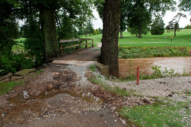 The floods from the Little Conewago Creek pulled dirt and asphalt at a bridge crossing at Grandview Golf Course on Wednesday, July 25, 2018. York County Ñ along with central Pennsylvania Ñ was  hit with almost 10 inches of rainfall that week.