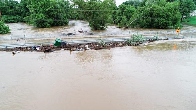 Flooding near Hersheypark shows debris next to bridge underwater.