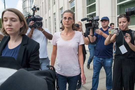 Clare Bronfman, center, is surrounded by reporters as she leaves Federal court, Tuesday, July 24, 2018, in Brooklyn. Clare Bronfman and three other people associated with the NXIVM organization had been charged with racketeering conspiracy.