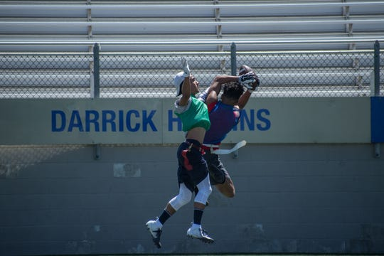 One of the Panthers' defensive players (blue) intercepts a pass during 7-on-7 scrimmages against the Eagles (green).