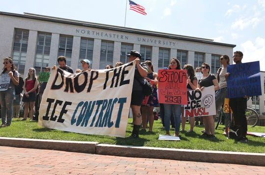 In this July 11, 2018 file photo, students and community activists rally at Northeastern University in Boston demanding the school cancel a multimillion-dollar research contract with U.S. Immigration and Customs Enforcement.