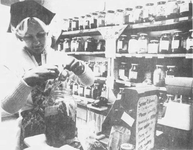 Helen Schuldt is seen in late 1978 filling a gallon herb jar at The Co-op Natural Foods.