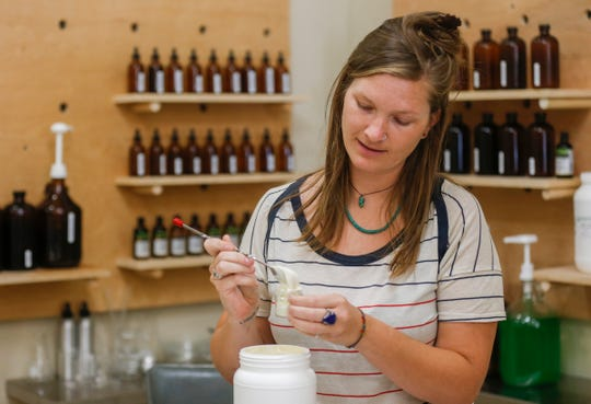 Anne Dezort, operator of The Bulk Soap Refill Station located at 210 S. Campbell Ave., fills a container with olive nourishing creme for a customer.