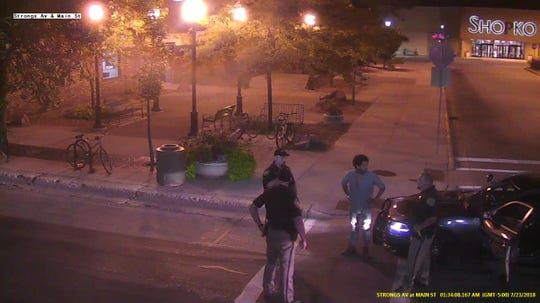 A frame from security camera footage shows Deandre Pettiford-Bates talking to officers from the Stevens Point Police Department and Portage County Sheriff's Office on Main Street in Stevens Point, Wis., in the early morning of Monday, July 23, 2018.