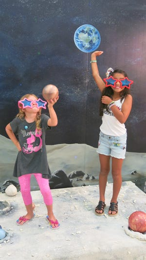 Vero Beach Museum of Art visitors enjoy pretending they are on the moon in the photo op area during the recent Star Party.