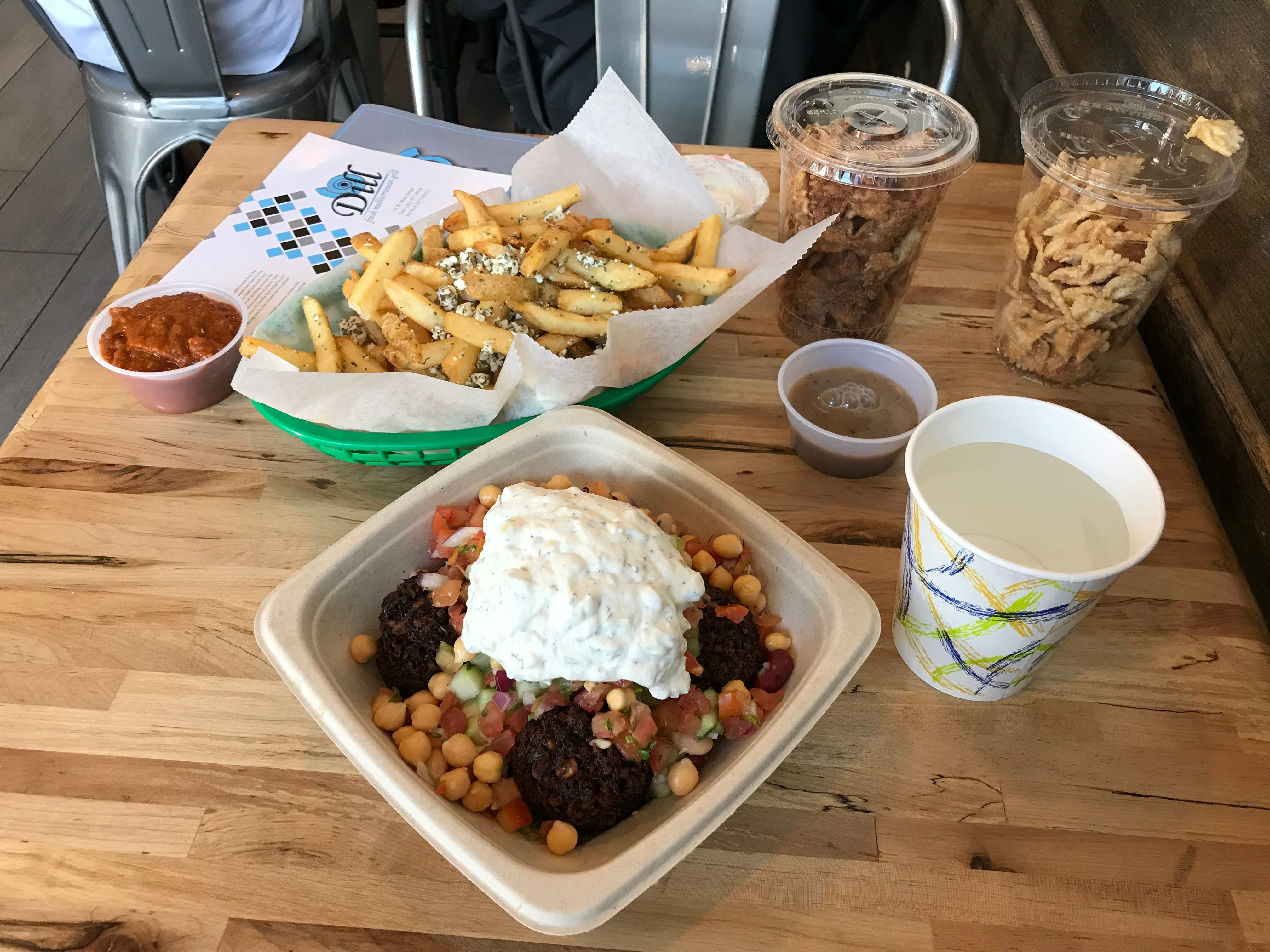 Greek fries and a falafel bowl at Dill Fresh Mediterranean Grill in New City. Photographed May 2018