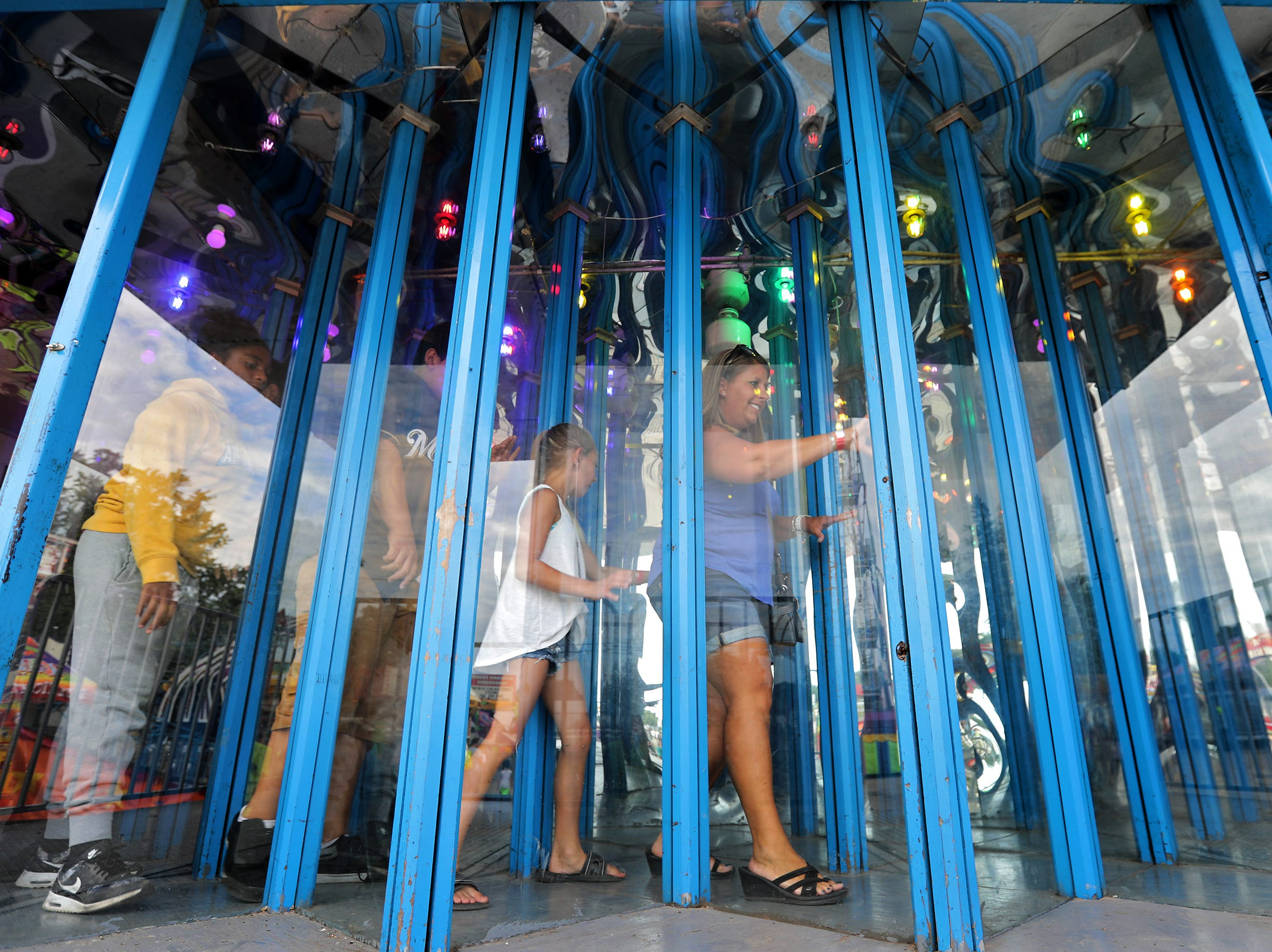 Heather, right and Khloe Thurber lead a group through the Glass House, house of mirrors, during the Outagamie County Fair on Wednesday, July 25, 2018 in Seymour, Wis. 