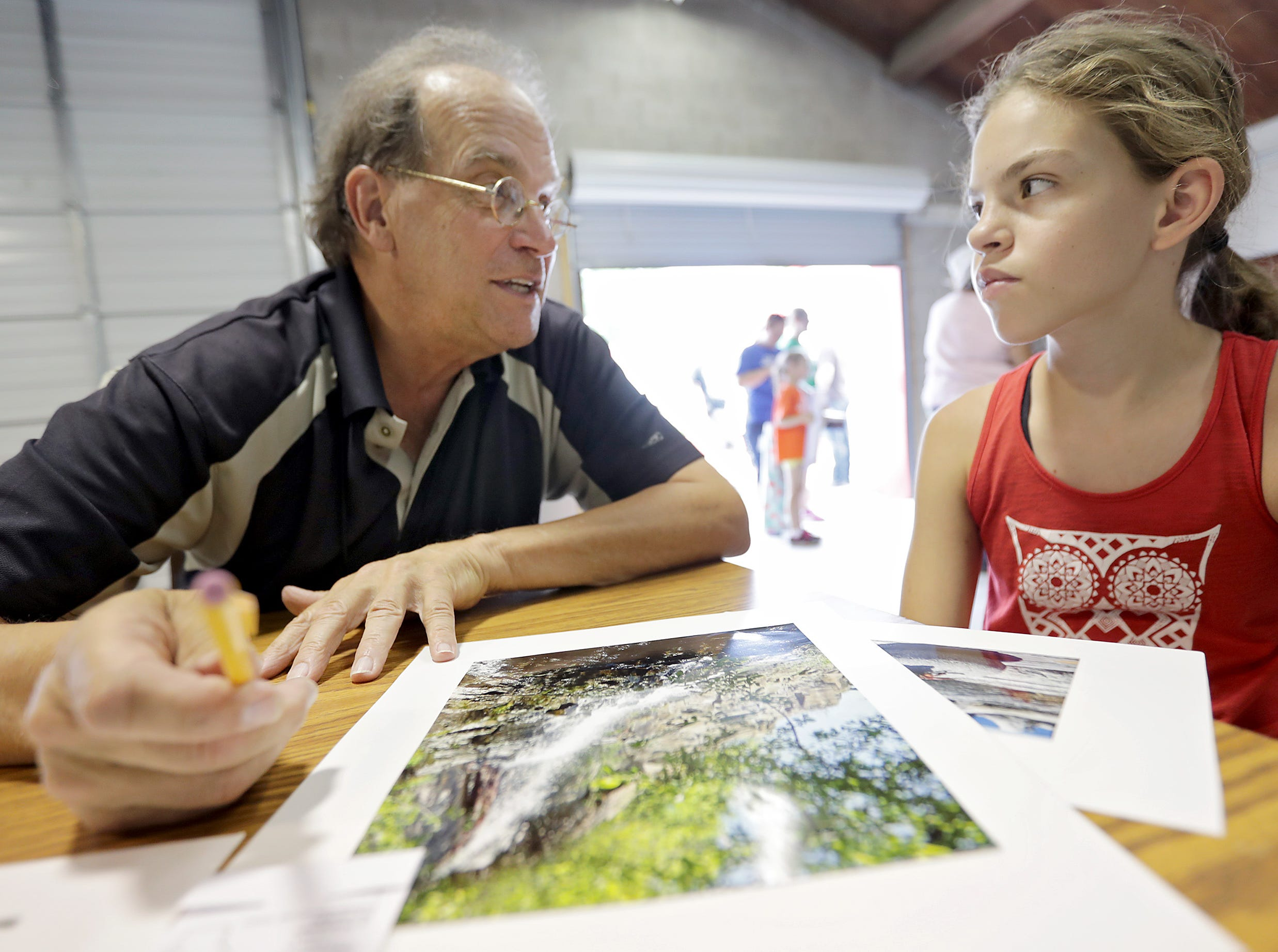 Judge Wayne Brabender critiques Alyna Johnson's photography submissions during the Outagamie County Fair on Wednesday, July 25, 2018 in Seymour, Wis. 