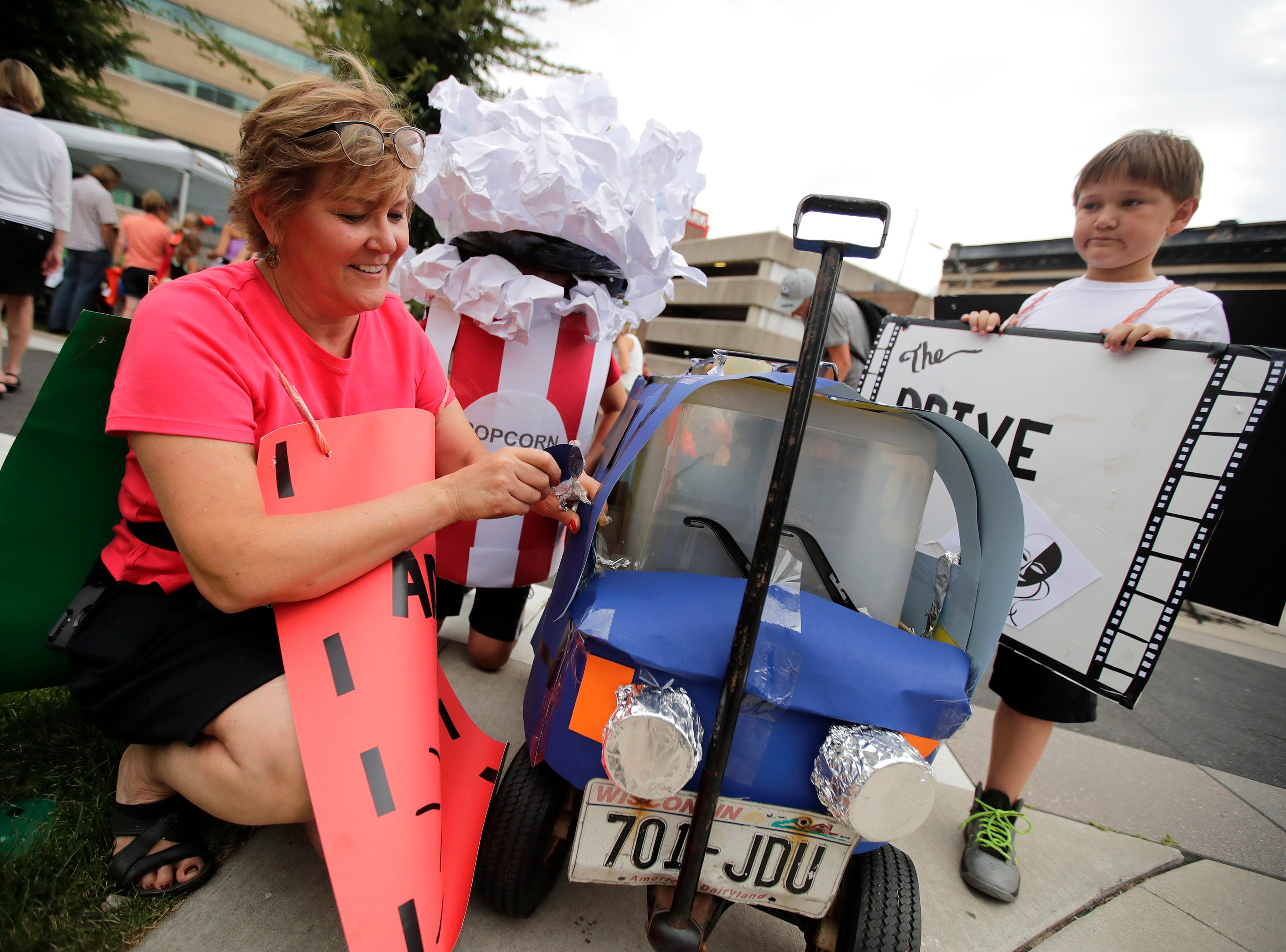 Michele VandenHeuvel, of Appleton, makes a repair to their float with her children John, 12, and Aaron, 9, during the 10th annual ChildrenÕs Parade Wednesday, July 25, 2018, in Appleton, Wis. Danny Damiani/USA TODAY NETWORK-Wisconsin