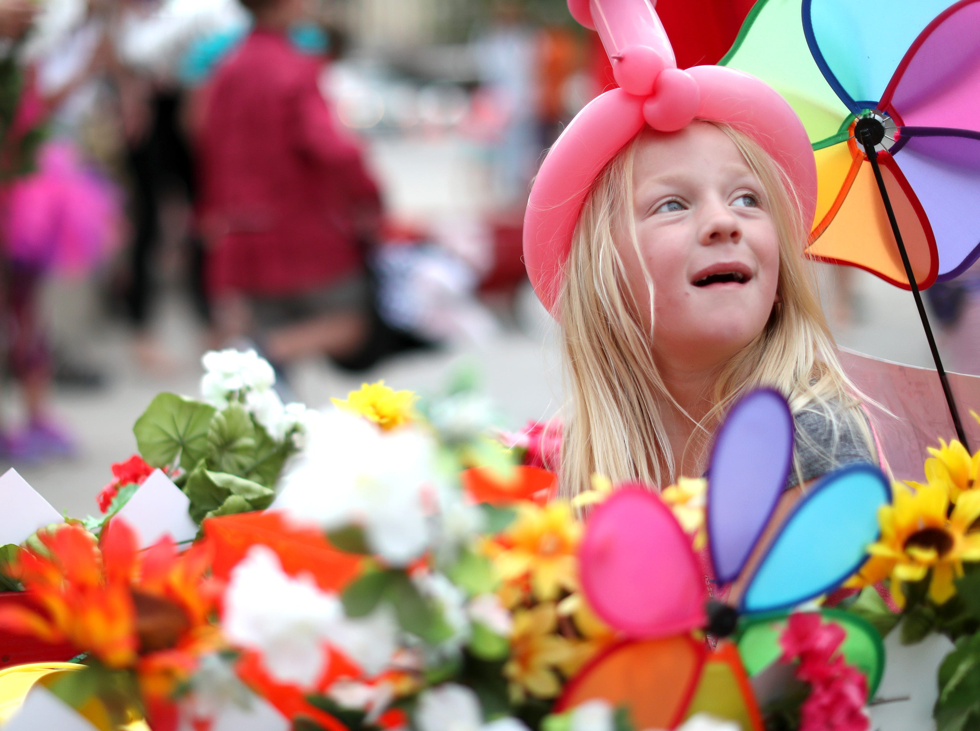 Aubrie Geurden, 5, sits in a wagon filled with flowers during the 10th annual ChildrenÕs Parade Wednesday, July 25, 2018, in Appleton, Wis. Danny Damiani/USA TODAY NETWORK-Wisconsin