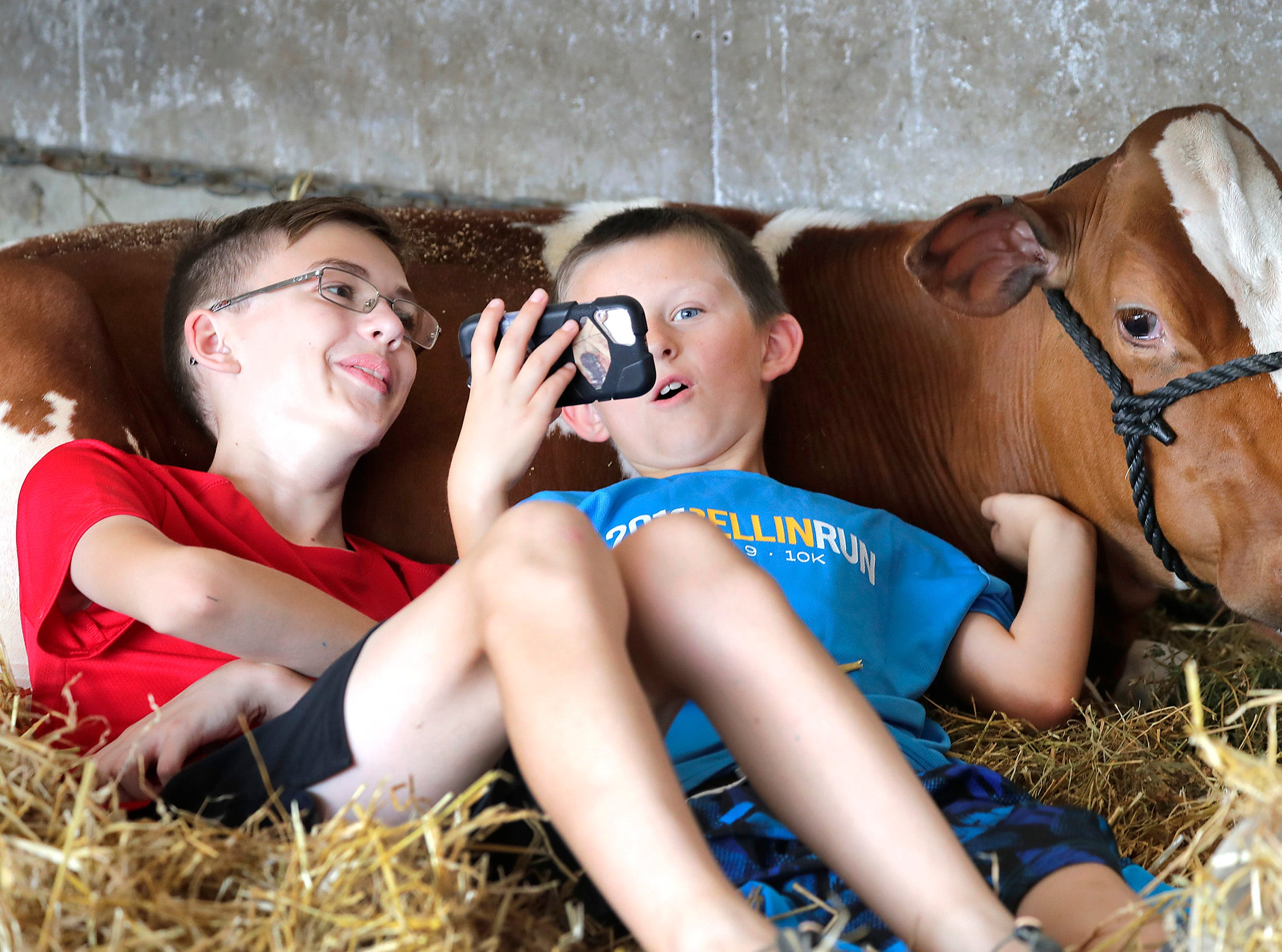 Adam Karweick, on left from Seymour, and Kody Banker, Black Creek, watch videos while relaxing during the Outagamie County Fair on Wednesday, July 25, 2018 in Seymour, Wis. 