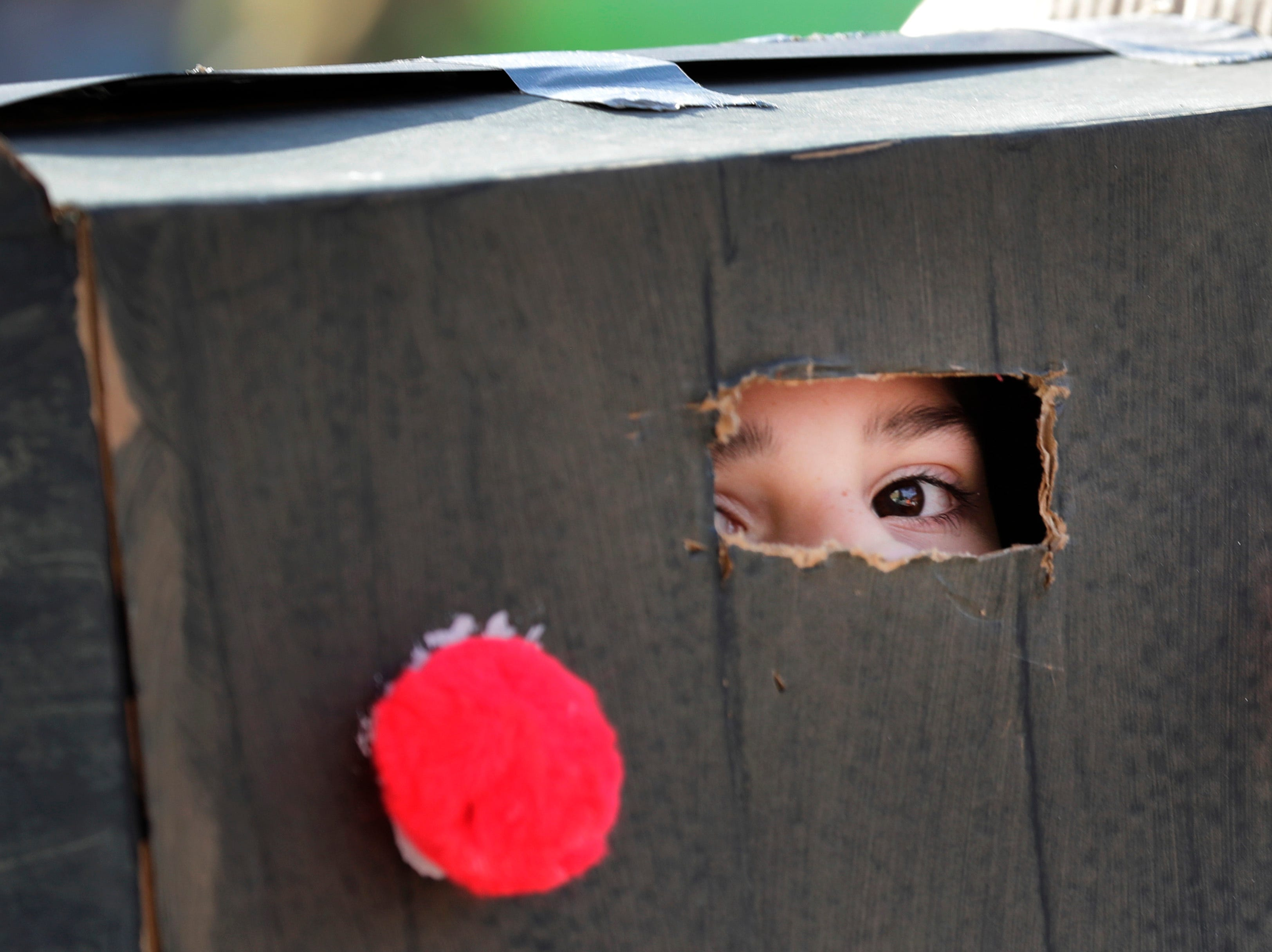 Claire Griffin, 9, peeks out of her homemade Godzilla costume during the 10th annual ChildrenÕs Parade Wednesday, July 25, 2018, in Appleton, Wis. Danny Damiani/USA TODAY NETWORK-Wisconsin
