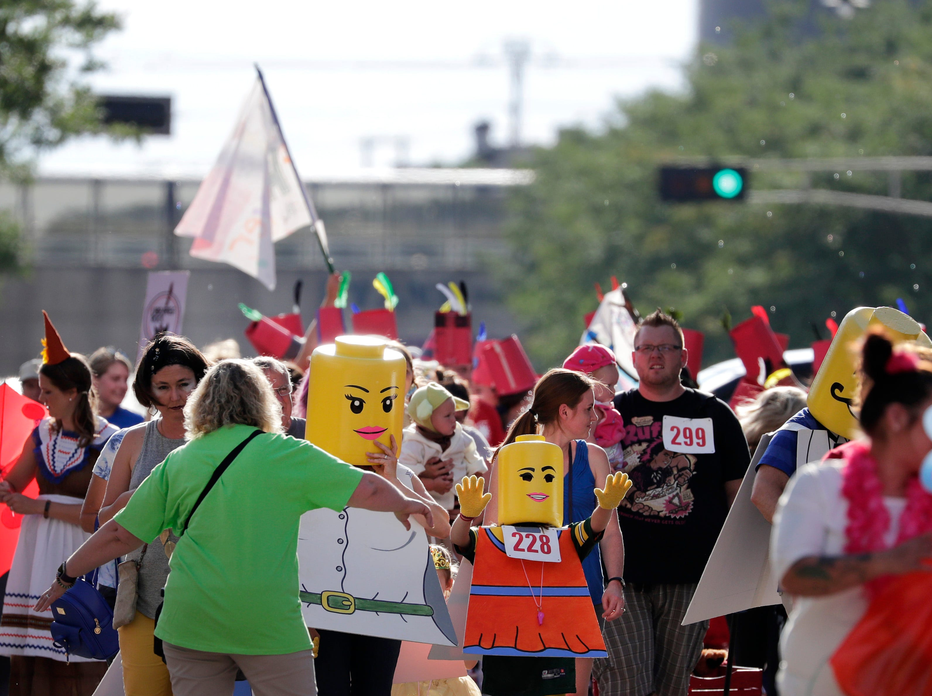 A family wearing Lego costumes makes their way down College Avenue during the 10th annual ChildrenÕs Parade Wednesday, July 25, 2018, in Appleton, Wis. Danny Damiani/USA TODAY NETWORK-Wisconsin
