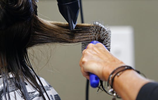 Owner Lori DeFalco works on the hair of a customer at Style Salon and Barber in Freehold Township.