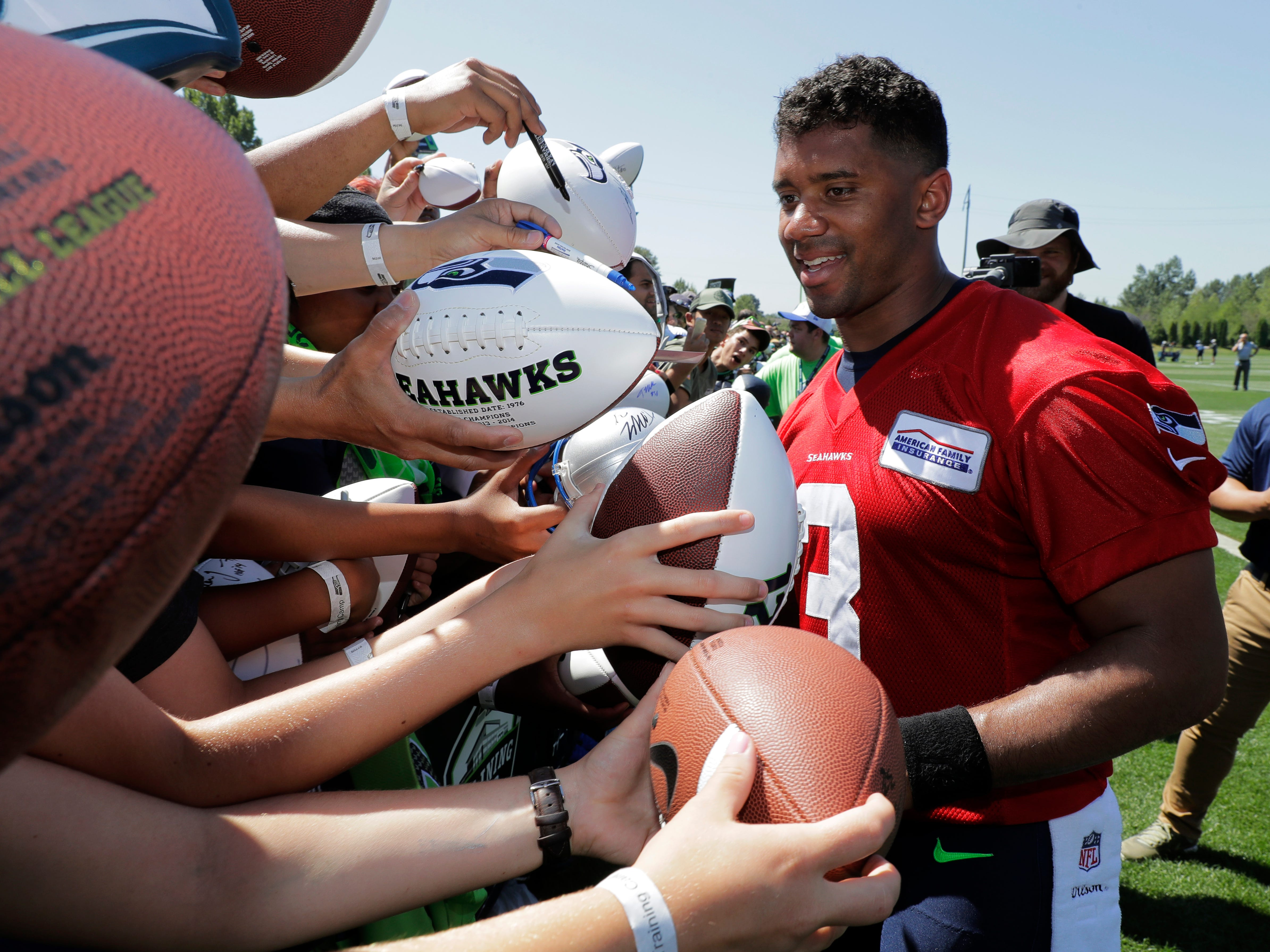 Seattle Seahawks quarterback Russell Wilson signs autographs after NFL football training camp, Thursday, July 26, 2018, in Renton, Wash. (AP Photo/Ted S. Warren)